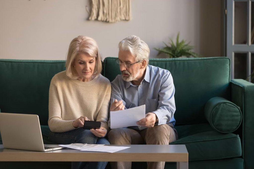 Äldre par med faktura vid dator